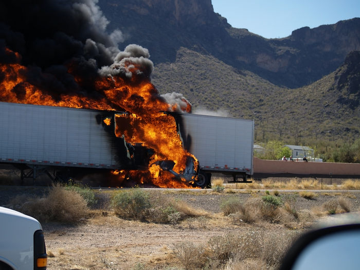 Taken in 2007, a semi-truck runs over a small car on Interstate Highway 10 in Arizona at Picacho Peak. The truck burst into flames because it was loaded with acid containers that ruptured. The accident closed the highway for 12 hours. Number of fatalities, if any, are unknown. Arizona Picacho, AZ Tragedy Accidents And Disasters Architecture Building Exterior Burning Damaged Day Destruction Environment Fire Fire - Natural Phenomenon Flame Heat - Temperature Land Vehicle Mode Of Transportation Motion Motor Vehicle Nature No People Outdoors Smoke - Physical Structure Transportation Truck