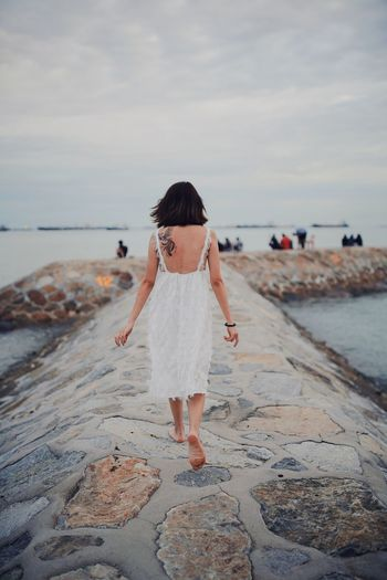Rear view of young woman standing by sea against sky