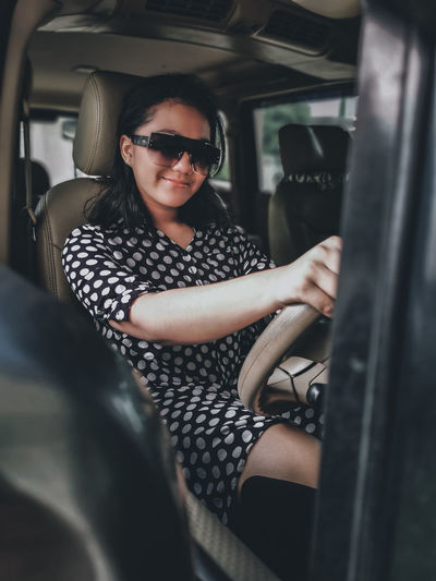 A girl wearing a polkadot dress, sun glasses and high boots sitting in a car