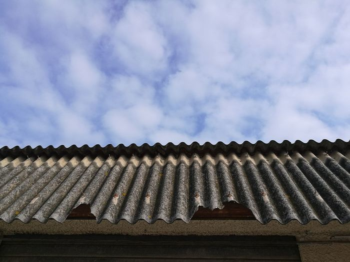 Low angle view of damaged roof against sky