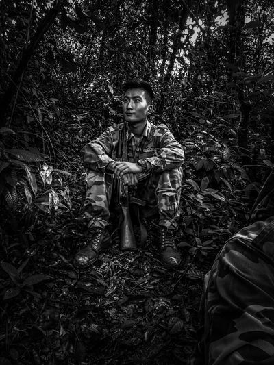 Thoughtful male army officer sitting in forest