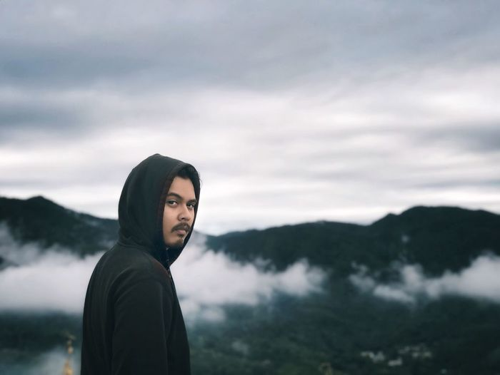 Portrait of man standing against mountains