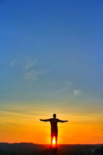 Silhouette man with arms outstretched standing against sky during sunset