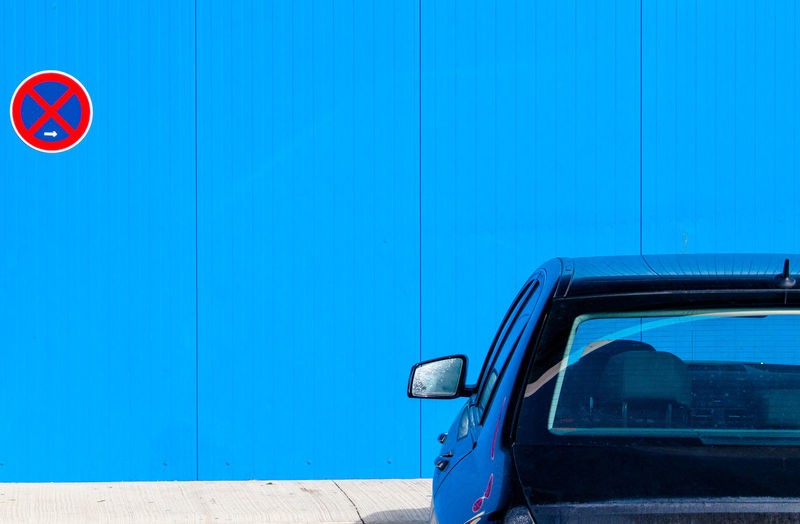 Close-Up Of Car Against Blue Wall
