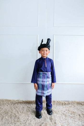 Portrait of cute boy wearing traditional clothing standing against wall
