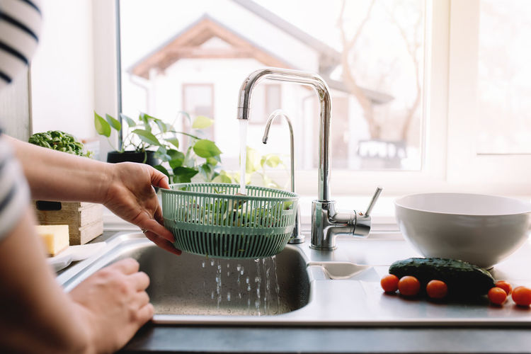 Woman washing green salad leaves for salad in kitchen in sink. high quality photo
