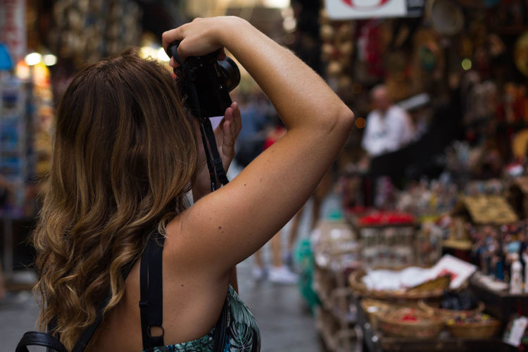 Side view of woman photographing at street market
