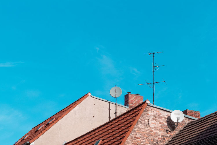 Architecture Roof Built Structure Building Exterior Antenna - Aerial Building Sky House Television Aerial Low Angle View Day Communication Technology Nature Satellite Blue Satellite Dish Residential District Telecommunications Equipment Roof Tile Wireless Technology No People Outdoors