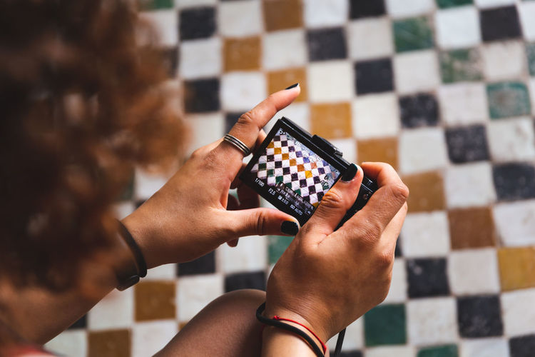 Cropped image of woman photographing tiled floor