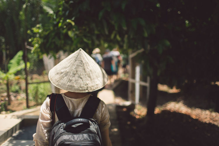Rear view of woman wearing asian style conical hat against trees