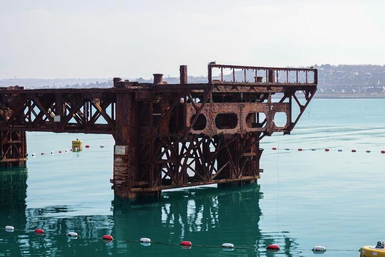 Abandoned bridge over sea against clear sky