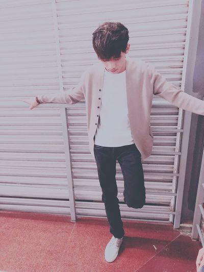 Young man with arms outstretched standing against wall