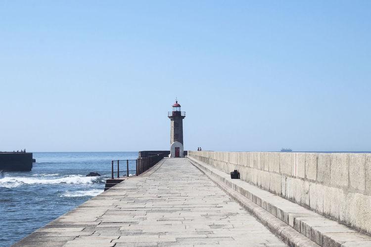 Lighthouse amidst sea and buildings against clear sky