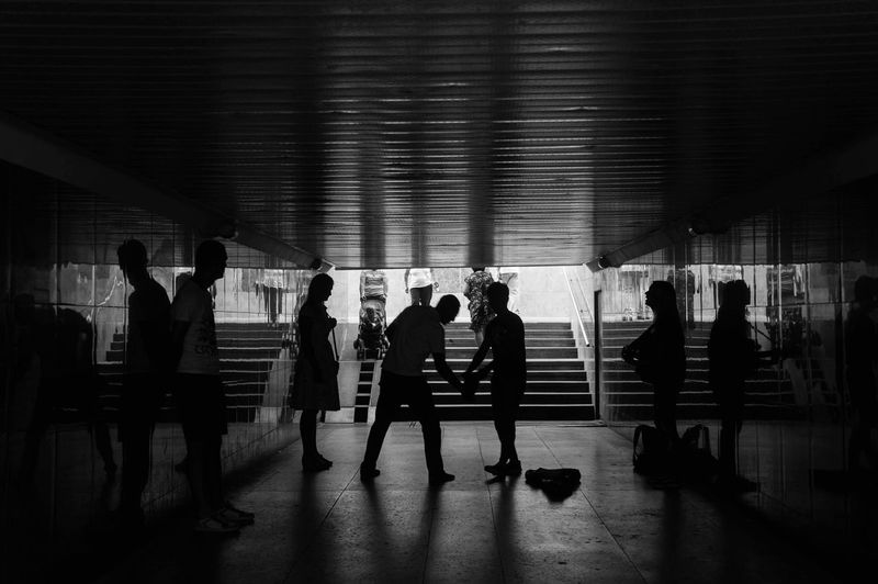 Silhouette people in underground walkway
