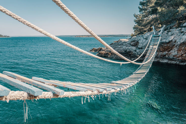 Cool rope bridge (Svjetionik bridge) over a cliff in Punta Christo. You definitely need to go there and try it! Pula, Croatia, Istria Travel Photography Croatia Travel Destinations Travel Water Sea Sky Nature Beauty In Nature No People Tranquility Waterfront Turquoise Colored Sunlight Travel Croatia Europe