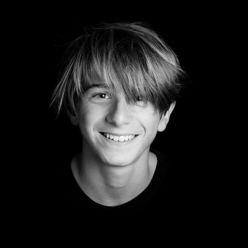 Portrait Of Smiling Teenage Boy Against Black Background