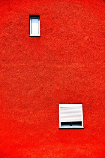 Close-up of windows on red wall