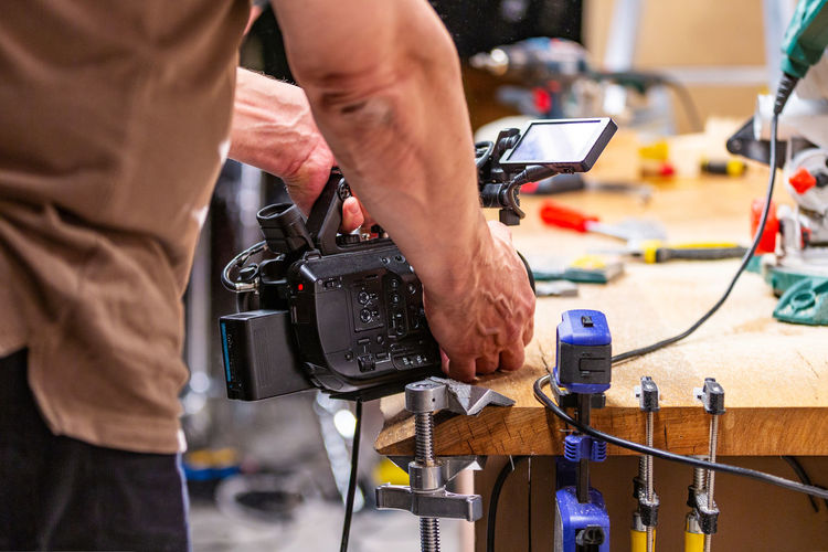 Midsection of man photographing in workshop