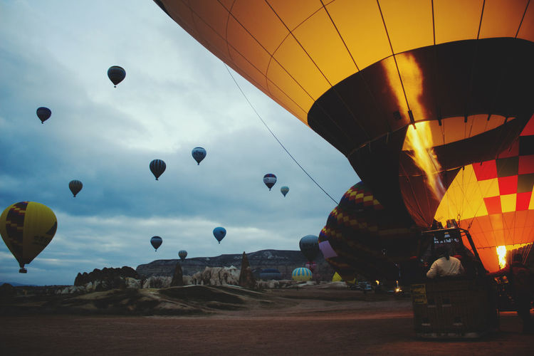 Hot air balloons against cloudy sky at cappadocia