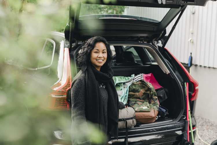 Portrait of smiling woman standing in car