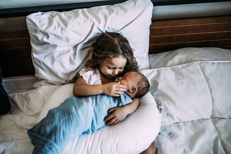 High angle view of siblings lying on bed