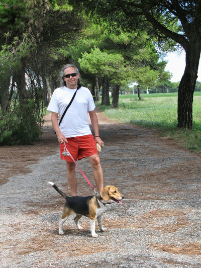 Portrait of man with dog standing in park