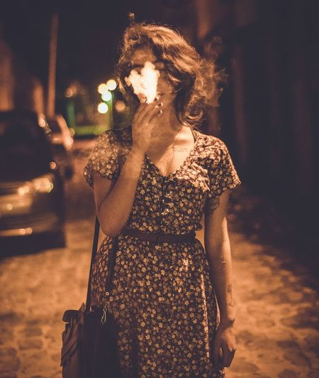 Young Woman Smoking On Street At Night