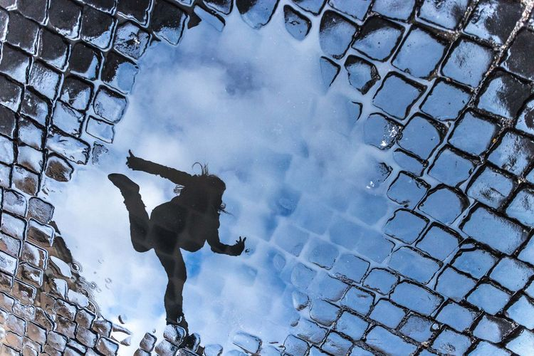 Reflection of woman jumping seen in puddle on street