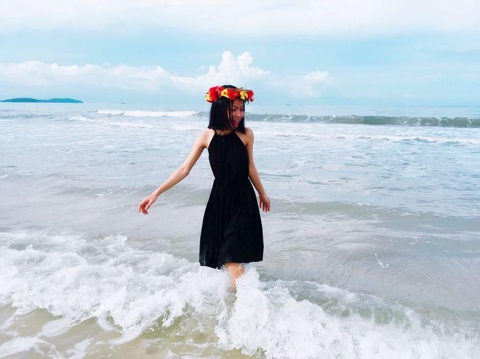 Young woman wearing flower tiara enjoying waves at beach