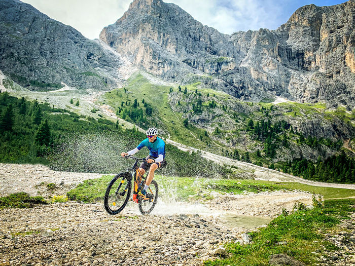 Man riding bicycle on field against mountain