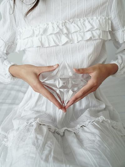 Midsection of woman holding heart shape on bed