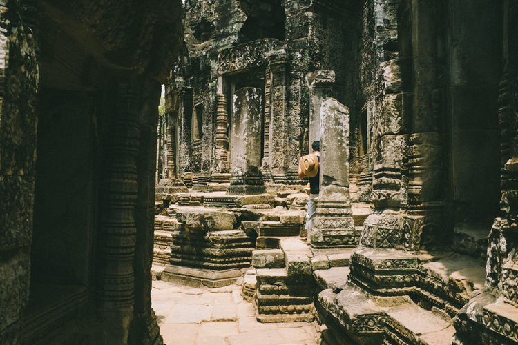 Rear view of man standing at old ruins temple