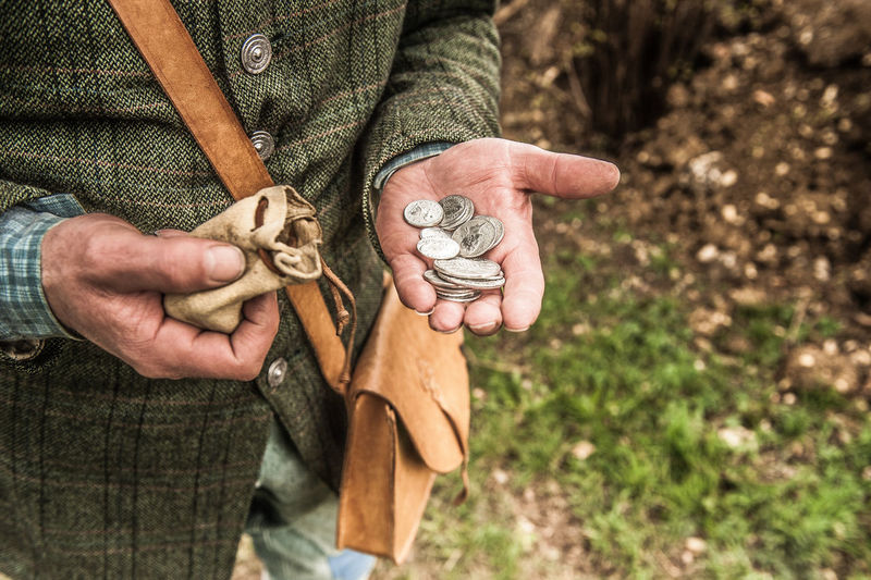 Midsection Of Man Holding Coins While Standing Outdoors