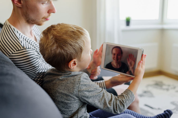 Father and son using mobile phone during video conferencing at home