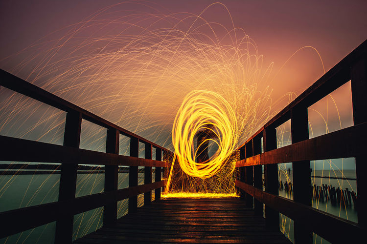 Railing Motion Night Illuminated Wire Wool Architecture Long Exposure Glowing Spinning Built Structure Orange Color Blurred Motion Nature Footbridge Bridge Burning Sky Fire No People Fire - Natural Phenomenon Bridge - Man Made Structure Outdoors Sparks