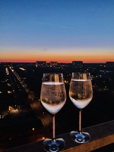 Close-up of wine glass on table against sky during sunset