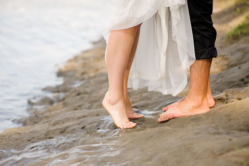 Low section of couple standing at beach