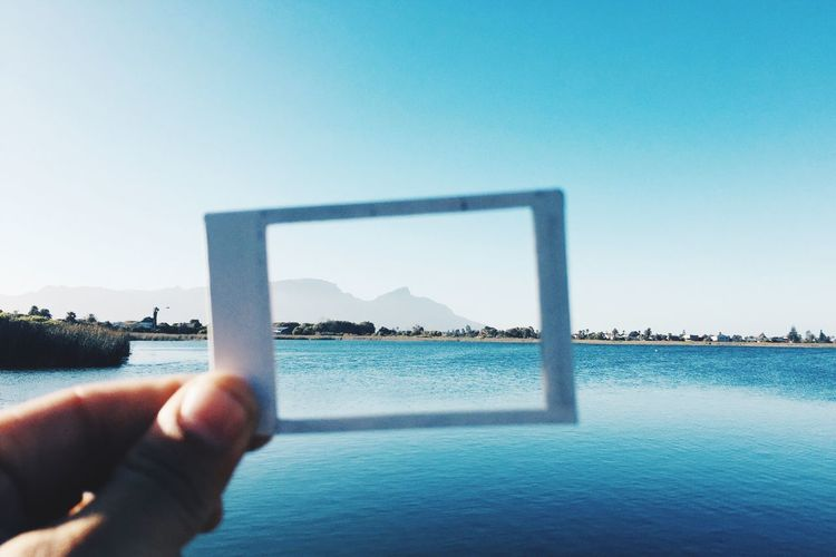 Cropped Image Of Hand Holding Picture Frame Against Sea