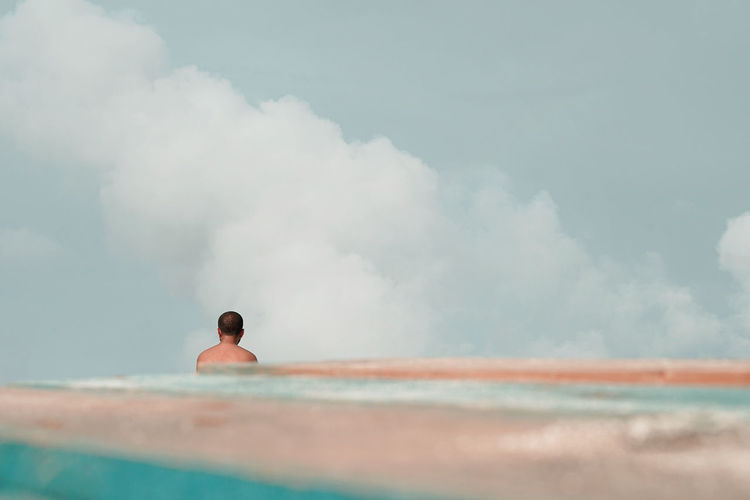 Rear view of man in swimming pool against sky
