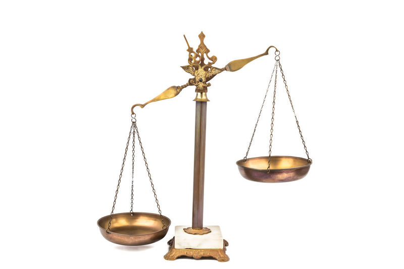 Conceptual of lopsided scale - unfair and unjust Bias Justice - Concept LIBRA Legal System Balanced Brass Equality Equilibrium Fairness Gold Colored Isolated On White Justice Law Lopsided No People Scales Studio Shot White Background