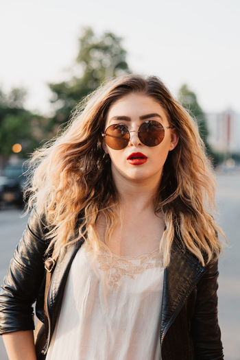 Portrait Of Young Woman Wearing Sunglasses Against Sky