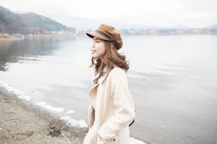 Water One Person Leisure Activity Standing Young Adult Young Women Lake Lifestyles Side View Casual Clothing Women Waist Up Looking Nature Day Hairstyle Looking Away Hair Beautiful Woman Contemplation Outdoors