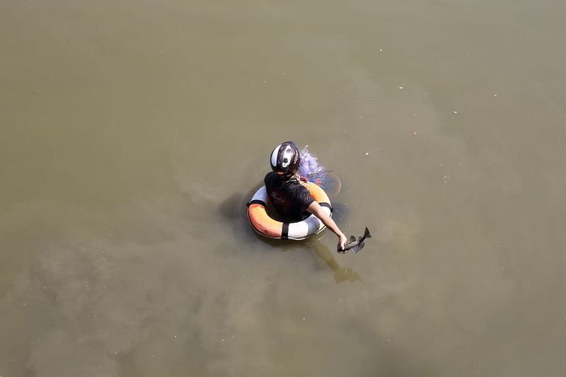 High Angle View Of Person Swimming With Inflatable Ring In Lake