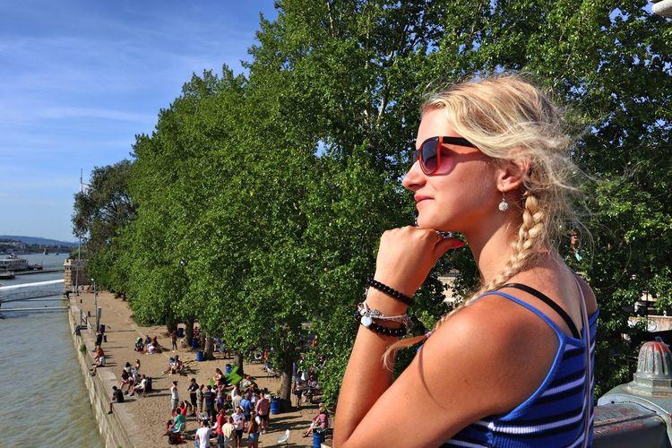 Beautiful woman wearing sunglasses looking away standing against trees