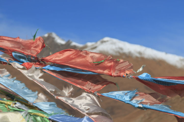 Close-up of prayer flags waving on mountain against clear blue sky