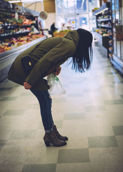Side View Of Woman Bending Over Floor At Supermarket