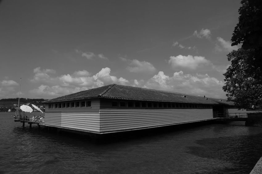 The Architect - 2017 EyeEm Awards Sky Water Cloud - Sky Outdoors Architecture Nature Lake People Real People Photography Outdoor Photography Black & White Blackandwhite Structures & Lines Structure Architecture Built Structure Cottage Lake View Lake Day Light And Shadow Illuminated