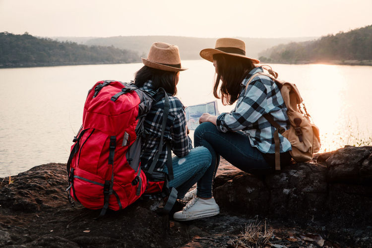 Travel Vacation Holiday Relaxing Rest Destination Nature Backpack Bag Journey Tourism Water Leisure Activity Lifestyles Real People Women Sky Sitting Togetherness Adult Friendship Lake People Outdoors Looking At View