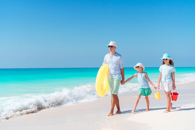 Father and daughters walking on beach