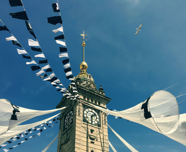 Low angle view of bird flying by clock tower with buntings against sky